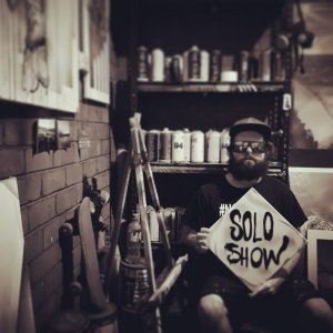 picture of jake graham sitting in garage before solo exhibition